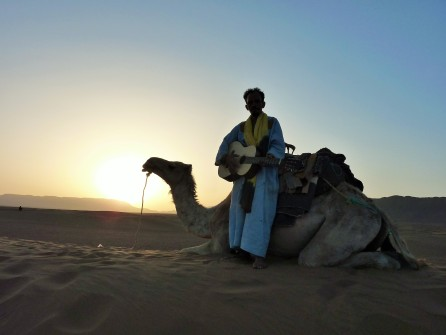 A berber man rests on his camel in the Sahara desert